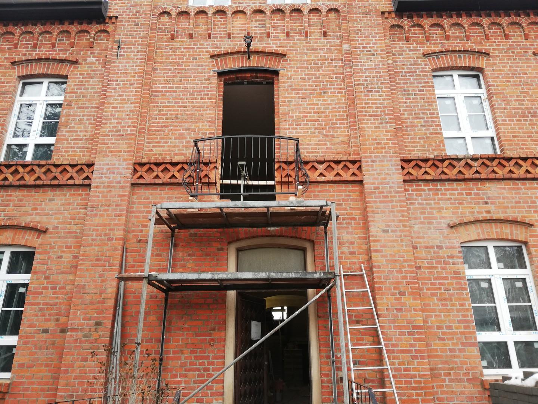 Montage des Rahmens mit der Balkonbrüstung über dem Eingang zum Gebäude