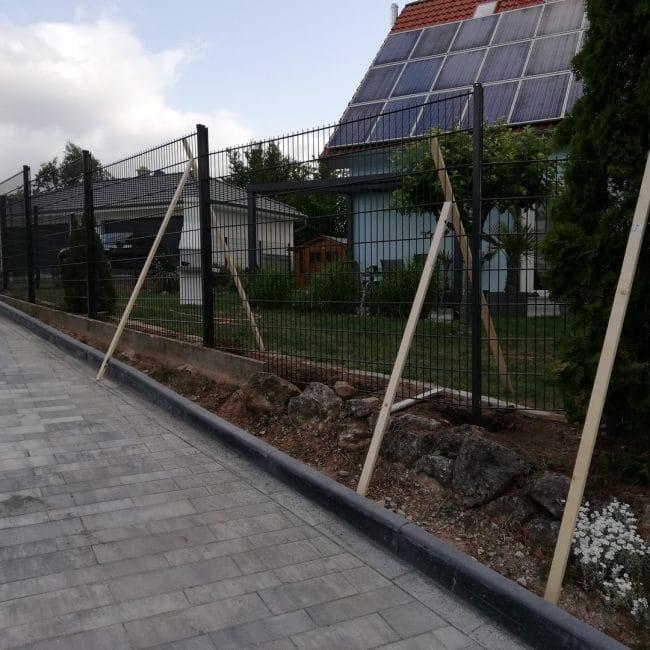 Aufstellen eines schwarzen Doppelstabzauns neben einem Haus mit Sonnenkollektoren