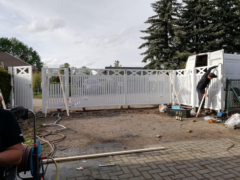 Installation eines weißen Metallzauns mit Tor und Eingangstor