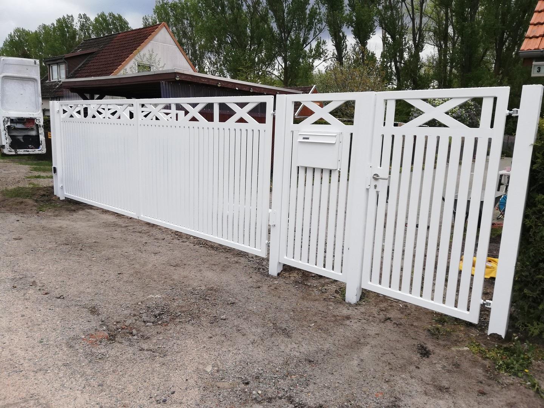 weißer Metallzaun mit Tor und Eingangstür