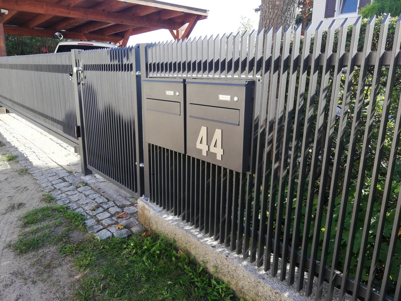 einfacher schwarzer Zaun mit 2 Kästen und schwarzem Tor und automatischem Tor