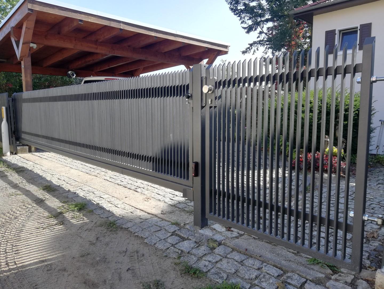 langes schwarzes automatisches Tor vor der Wohnung zusammen mit einem schwarzen Tor