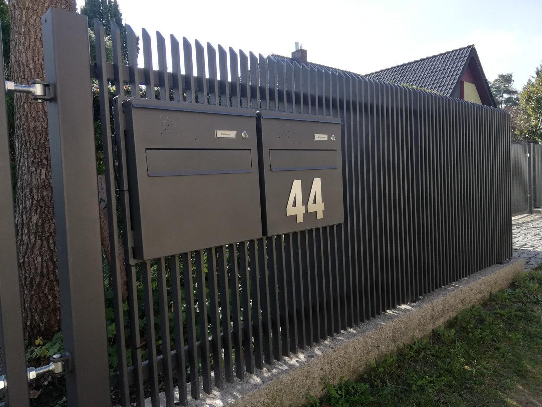 schöner schwarzer Metallzaun mit zwei Briefkästen