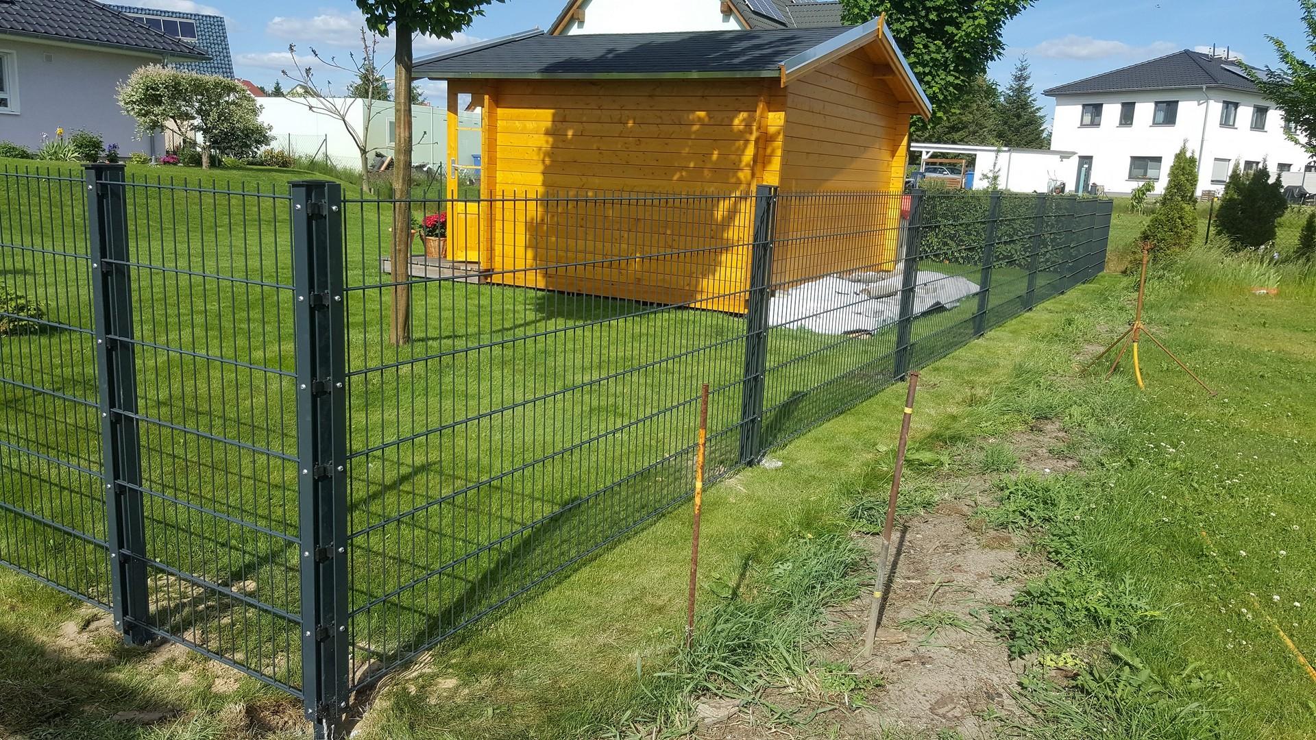 gelbes Häuschen umzäunt mit einfachem Doppelstabmattenzaun