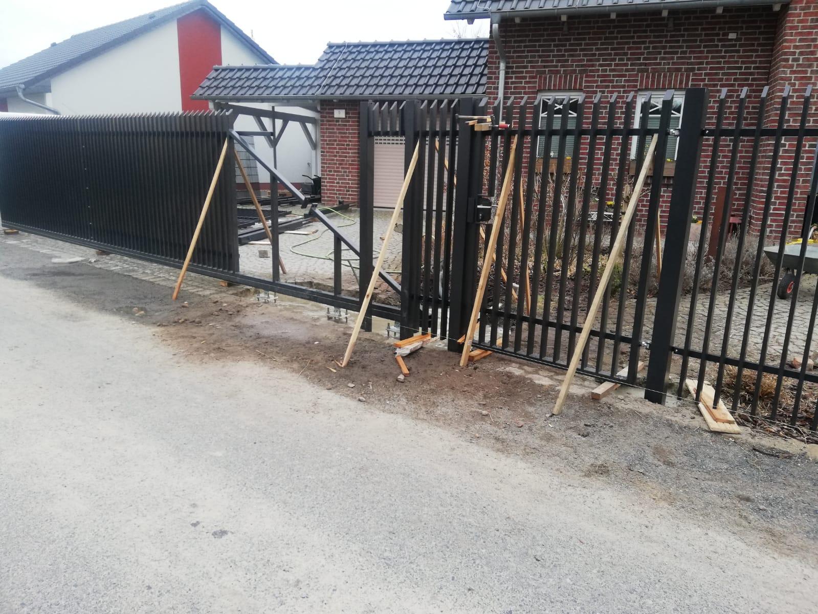 Montage eines schwarzen Zauns mit Fell und Eingangstor