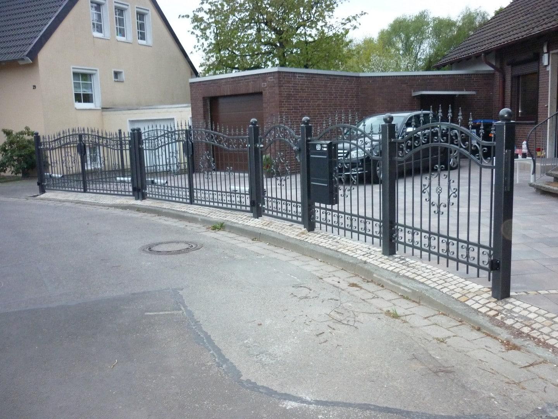 schwarzer schmiedeeiserner Zaun vor dem Haus mit Tor und zwei Ausgangstoren