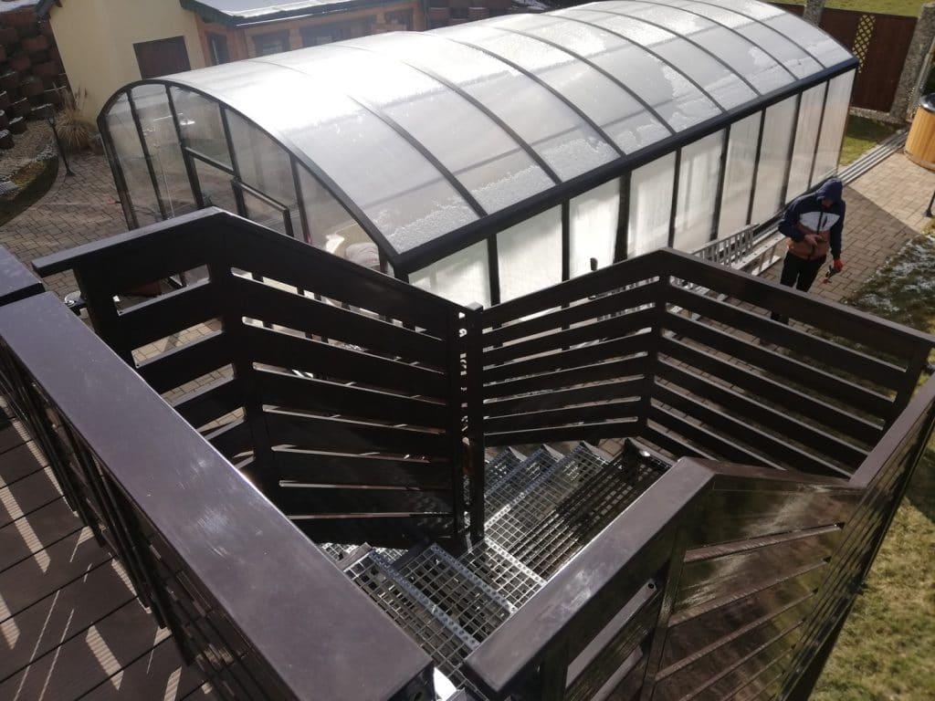 ein schönes braunes Treppengeländer in der Nähe eines kleinen Gewächshauses