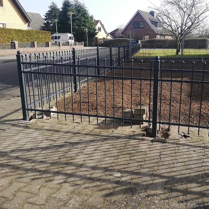 Schwarz verzierter Zaun um den Hinterhof