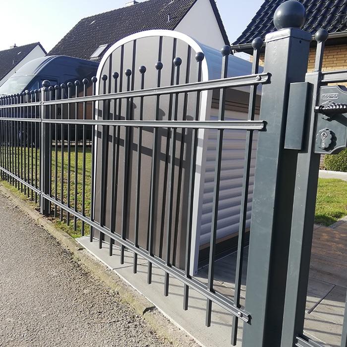 schwarzer Metallzaun mit einem Tor um das Haus