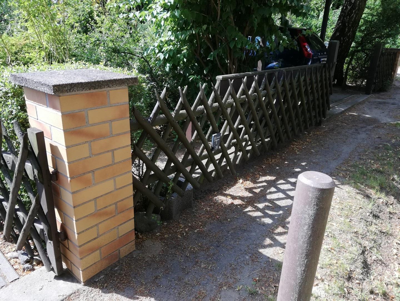 alter brauner Zaun mit Eingangstor vor dem Austausch gegen einen neuen